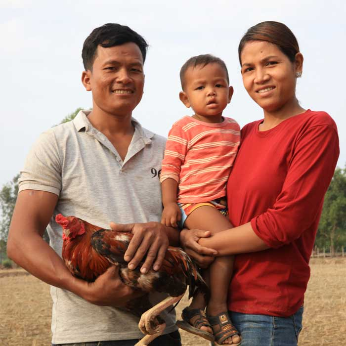 Cambodian farmer family with mother holding baby and father holding chicken