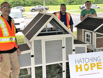 Three men stand around two newly built chicken coops with sign for Hatching Hope